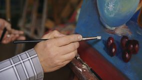 Feche acima da mão do ` s do homem que pinta ainda a imagem da vida na lona no estúdio da arte Fotografia de Stock