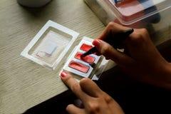Feche acima da mão do ` s da mulher que aplica a composição com cosmético foto de stock