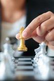 Feche acima da mão do tiro da mulher de negócio que guarda o betwee dourado da xadrez Imagem de Stock Royalty Free