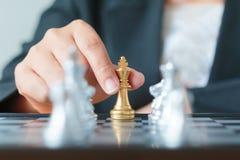 Feche acima da mão do tiro da mulher de negócio que guarda o betwee dourado da xadrez Foto de Stock