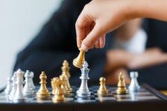 Feche acima da mão do tiro de xadrez dourada movente da criança para derrotar e de ki Fotos de Stock Royalty Free