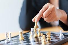 Feche acima da mão do tiro de xadrez dourada movente da mulher de negócio ao defe Fotografia de Stock Royalty Free