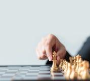 Feche acima da mão do tiro de xadrez dourada movente da mulher de negócio ao defe Imagens de Stock