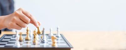 Feche acima da mão do tiro de xadrez dourada movente da mulher de negócio ao defe Foto de Stock Royalty Free