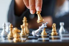 Feche acima da mão do tiro de xadrez dourada movente da mulher de negócio ao defe Foto de Stock