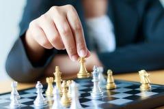 Feche acima da mão do tiro de xadrez dourada movente da mulher de negócio ao defe Imagem de Stock