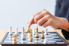 Feche acima da mão do tiro de xadrez dourada movente da mulher de negócio ao defe Fotos de Stock Royalty Free