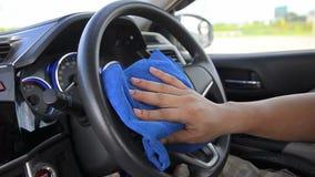 Feche acima da mão do tiro do homem que usa a micro tela azul da fibra para limpar o volante filme