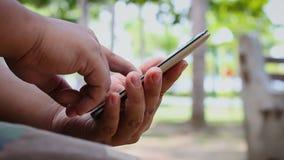 Feche acima da mão do tiro do homem que usa o telefone esperto móvel no parque público da natureza com som ambiental video estoque