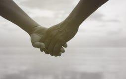 Feche acima da mão dos pares superiores que mantêm a mão unida perto do beira-mar na praia, cor preto e branco da imagem Fotografia de Stock Royalty Free