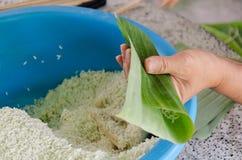Feche acima da mão e das bananas com arroz pegajoso Khao Tom Mat fotografia de stock