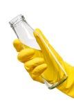 Feche acima da mão fêmea na luva de borracha protetora amarela que guarda a garrafa de leite de vidro transparente limpa vazia fotos de stock royalty free