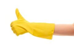 Feche acima da mão fêmea na luva de borracha protetora amarela que mostra os polegares acima do sinal Imagem de Stock