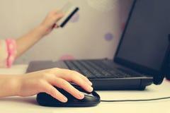 Feche acima da mão fêmea no rato e em guardar do computador um cartão de crédito Fotos de Stock Royalty Free