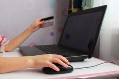 Feche acima da mão fêmea no rato e em guardar do computador um cartão de crédito Fotografia de Stock
