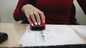 Feche acima da mão fêmea que põe um selo no contrato ou nos documentos filme
