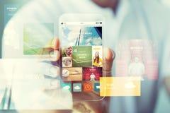 Feche acima da mão masculina com notícia no smartphone Fotos de Stock Royalty Free