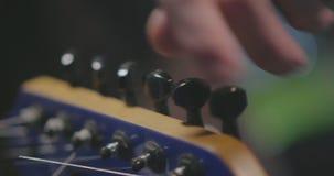 Feche acima da mão masculina que ajusta sua guitarra elétrica video estoque