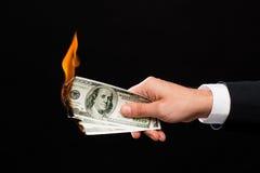 Feche acima da mão masculina que guarda dinheiro ardente do dólar Fotografia de Stock Royalty Free