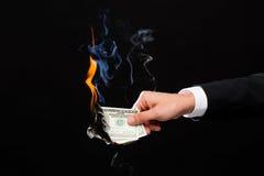 Feche acima da mão masculina que guarda dinheiro ardente do dólar Imagens de Stock