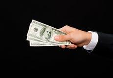 Feche acima da mão masculina que guarda o dinheiro do dinheiro do dólar Foto de Stock Royalty Free