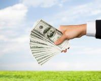 Feche acima da mão masculina que guarda o dinheiro do dinheiro do dólar Fotos de Stock Royalty Free