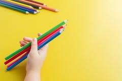 Feche acima da mão da menina que guarda o lápis da cor em Backgro amarelo imagens de stock