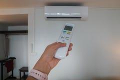 Feche acima da mão da mulher com controlo a distância do condicionador de ar para o ajuste de temperatura imagens de stock royalty free