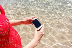 Feche acima da mão da mulher que guarda o smartphone e tome a foto que está no mar imagem de stock royalty free