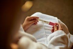 Feche acima da mão da mulher que guarda um teste de gravidez home positivo fotografia de stock royalty free
