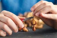Feche acima da mão da mulher que rosqueia grânulos no cordão para fazer a colar ou o bracelete artístico do grânulo fotos de stock royalty free