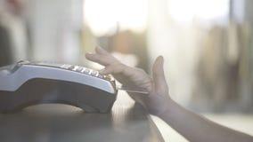 Feche acima da mão da mulher s que paga com um cartão de crédito em uma loja Fotografia de Stock Royalty Free