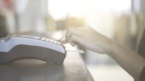 Feche acima da mão da mulher s que paga com um cartão de crédito em uma loja Fotos de Stock Royalty Free