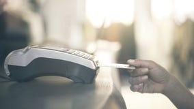 Feche acima da mão da mulher s que paga com um cartão de crédito usando uma máquina portátil na loja Feche acima do tiro Imagem de Stock Royalty Free