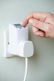 Feche acima da mão que ajusta o interruptor do temporizador no soquete da tomada imagem de stock