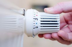 Feche acima da mão que ajusta o termostato do aquecimento fotografia de stock