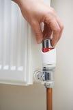 Feche acima da mão que ajusta o termostato do aquecimento fotos de stock royalty free