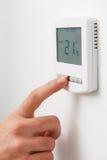 Feche acima da mão que ajusta o termostato do aquecimento central de Digitas fotos de stock