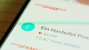 Feche acima da mão que consulta através dos email do Spam em uma tela do smartphone video estoque