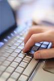 Feche acima da mão que datilografa no teclado de laptop Fotos de Stock