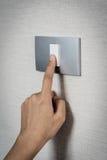 Feche acima da mão que gira de ligar/desligar no interruptor da luz cinzento imagem de stock