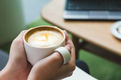 Feche acima da mão que guarda o copo de café quente do cappuccino com latte do coração imagens de stock