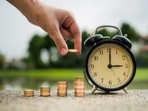 Feche acima da mão que põe o dinheiro à pilha de moedas com tempo, valor de época do conceito do dinheiro no tema da finança do n imagem de stock royalty free