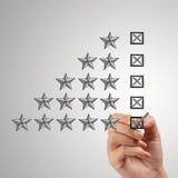 Feche acima da mão que põe uma marca de verificação sobre uma avaliação de cinco estrelas Foto de Stock