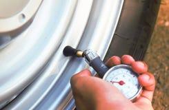 Feche acima da mão que verifica o ar em um pneu de carro Fotos de Stock Royalty Free