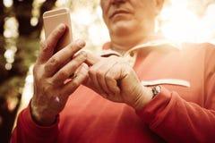 Feche acima da mão superior no parque usando o telefone celular foto de stock