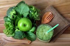 feche acima da maçã verde com o vegetal verde misturado e do suco verde Foto de Stock