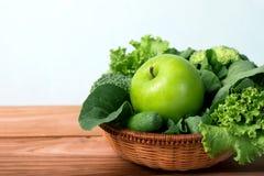 feche acima da maçã verde com o vegetal verde misturado na cesta e Imagem de Stock
