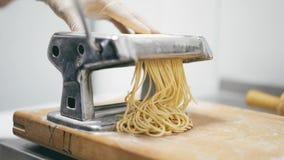 Feche acima da massa fresca dos espaguetes que sai da máquina da massa video estoque