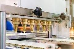 Feche acima da massa ou do creme e proveja de bocal a descarga do biscoito ou dos doces automáticos que fazem a máquina na linha  imagem de stock royalty free